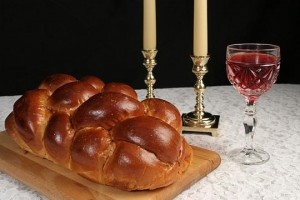 Braided challah, two candles and a cup of wine on white tablecloth